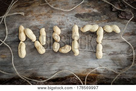 The Inscription Of Peanuts On Aged Wood