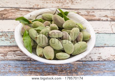 Fresh green unripe almonds on white plate in vintage table
