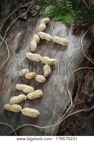 The Inscription Of Peanuts On Aged Wood