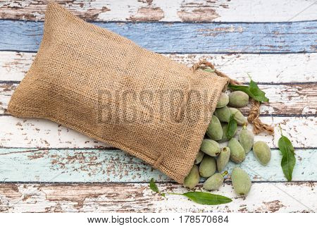 Unripe almonds in bag on vintage table from top view