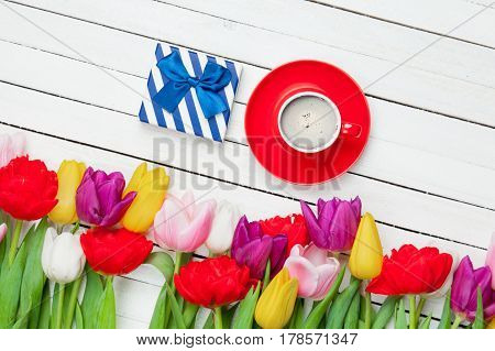 Photo Of Cup Of Coffee, Cute Gift And Colorful Tulips On The Wonderful White Wooden Background