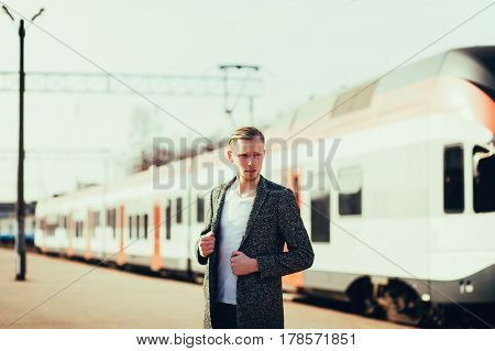 Handsome young man standing in coat at a modern train station