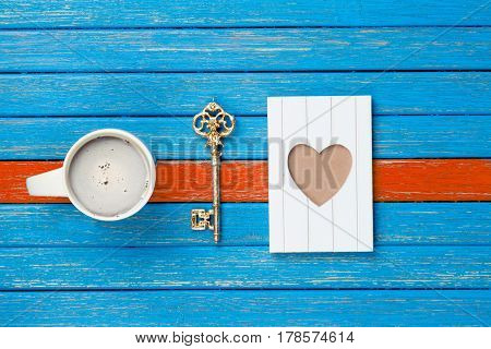 photo of cup of coffee golden key and postcard on the wonderful wooden background in pop art style