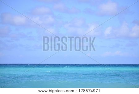 alligned horizon with turquoise sea in a color gradation from baby blue to royal blue and a baby blue sky with white cumulus clouds with purple contour.