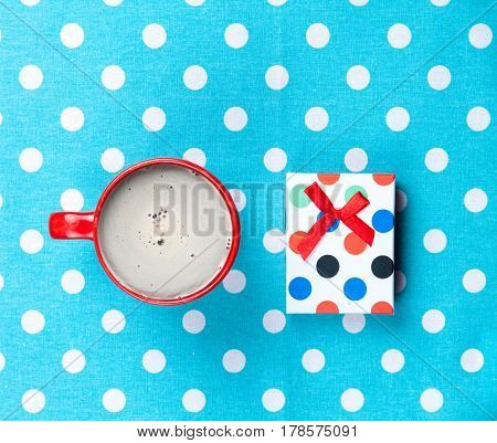 Photo Of Cup Of Coffee And Cute Gift On The Wonderful Blue Dotted Background