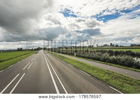 Country road with beautiful markings, against a contrasting cloudy sky. Netherlands.