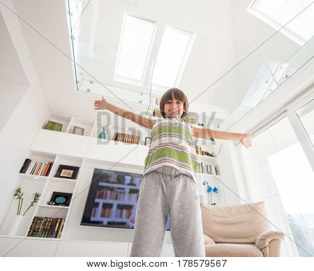 Child with open hands in modern interior of living room
