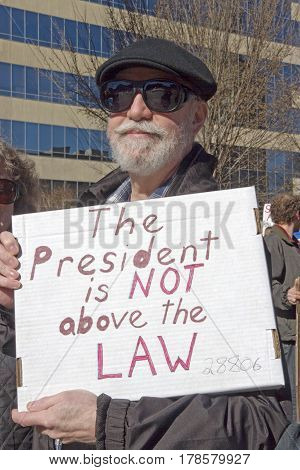 Asheville North Carolina USA - February 25 2017: Senior man at a rally for Obamacare holds a sign saying