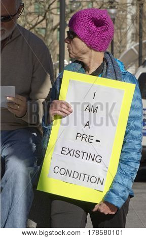 Asheville, North Carolina, USA - February 25, 2017: Senior female activist wearing a pink knit Pussyhat symbolic of women's solidarity and empowerment holds a sign saying