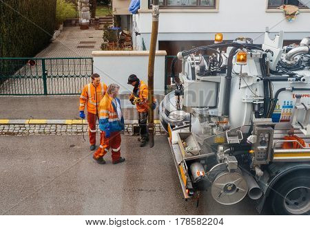 PARIS FRANCE - DEB 10 2017: Team of wWorkers using sewerage truck and large pipe working on the clogged street rain water drain repairing and maintenance
