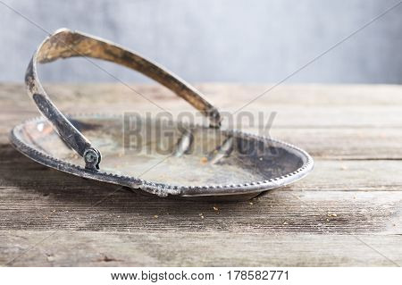 The old darkened metal dish on a wooden table. The vase for cookies from metal deformed and which has turned black costs on not colored table from gray boards. Vintage rural style copyspace on the right