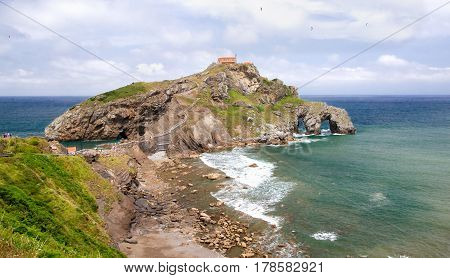 View from the coast on the rock in the ocean with a chapel Doniene Gaztelugatxeko. A chapel Doniene Gaztelugatxeko chapel (San Juan - Gastelugache) in the Basque Country northern Spain in the sunny summer day against the blue sky with plumose clouds