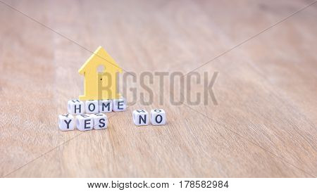 HOME YES NO horizontal word of cube letters with green house symbol on wooden surface.