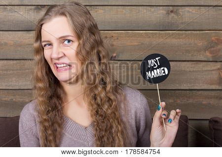 Woman with disgusted face holding icon on a stick