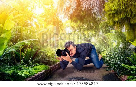 Male squat, photographing green nature on camera
