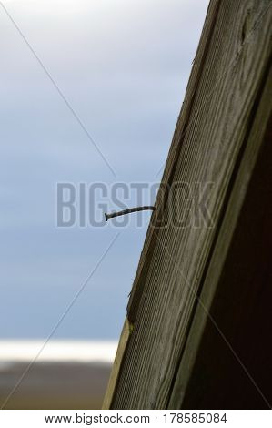 single bent nail along roof line of beach house