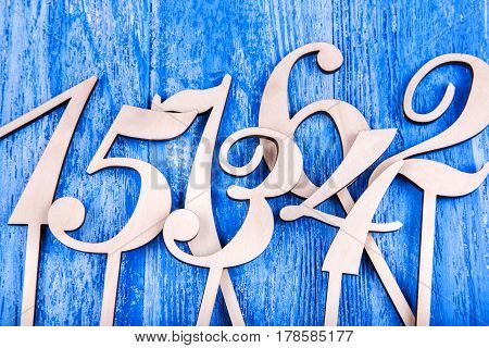 wooden numbers one two three four five six seven scattered on a blue wooden background top view