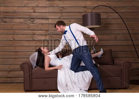 Groom trying to choke bride in white dress