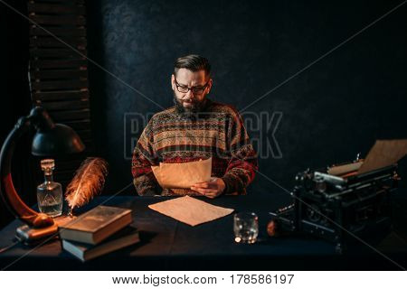 Writer in glasses reading his literature text