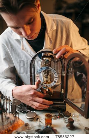 Watchmaker holding old table clock
