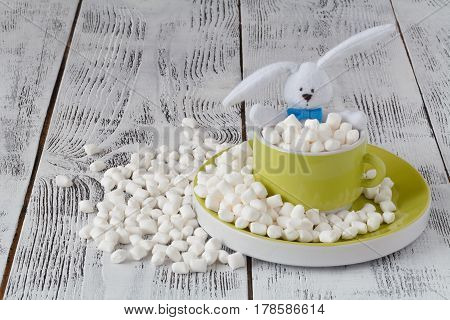 Cup Full Of Marshmallow That Crumble On A Wooden Background. Toy In Cup.