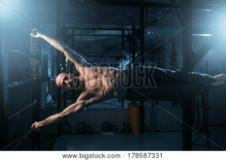Athlete with muscular body training on bar