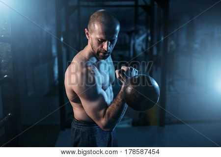 Muscular man exercises with kettlebell on training