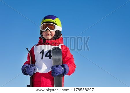 Close-up portrait of happy kid boy holding skis in his hands against blue sky