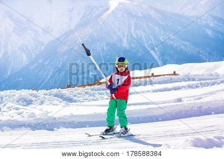Young skier going uphill in the mountains using a surface lift on the slope