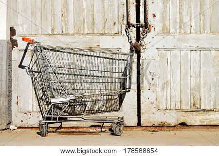 shopping trolley from the supermarket, left in front of the old  latched doors