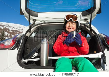 Portrait of happy skier sitting in the car boot and drinking warm tea from thermos bottle
