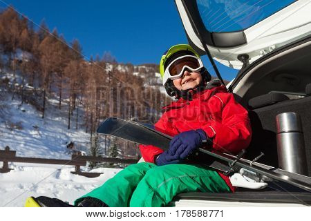 Close-up portrait of cute boy in safety helmet and mask sitting in the car boot, having rest after skiing