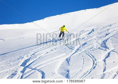 Portrait of male skier running downhill on slope at sunny day