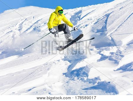 Male skier launching of mogul jumping and hitting the slopes