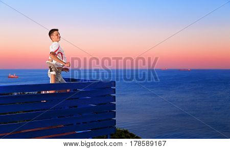 Happy boy jumping on the background of the sea at sunset