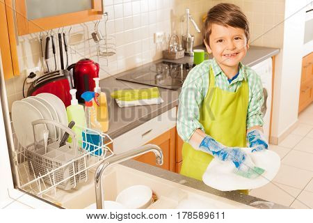 Little young small boy cleaning dishes in the kitchen with mop and soap wearing apron smiling to camera