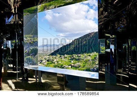 looking out a mirrored window at desert landscape