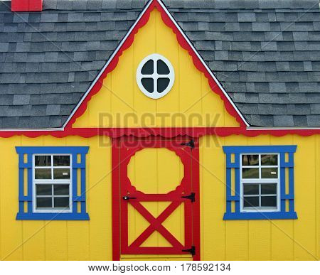 Colorful Yellow Wooden Playhouse with Red and Blue Trim