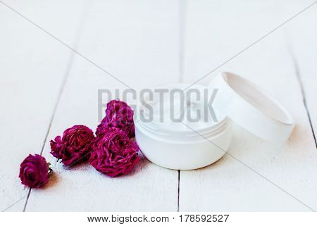 Cream for dry skin in a white jar with dry flowers of pink roses on a white wooden table