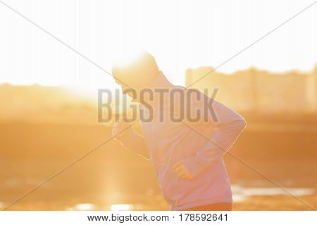 A Young Man  Runs In The Morning At Sunrise. Play Sports And Lead An Active Lifestyle. Low Contrast