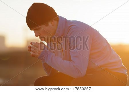 A Young Man In Sports Clothes Resting After Jogging, Trying To Regain Breath And Warm His Palms