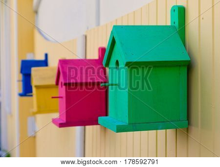 Colorful bird houses on a fence.