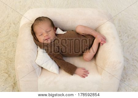 One week old newborn baby of mixed race relaxing on a soft couch