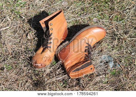 leather bright orange color lady's boots lay off on the grass