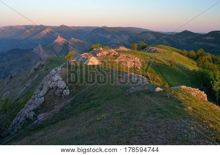 Summer landscape. Tourist tent on a camping in the mountains. Sunny morning