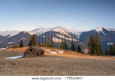 Spring landscape with an old wooden barn. Dawn in a mountain village. View of the peaks. Carpathians, Ukraine, Europe