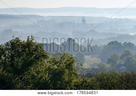 Summer landscape with a morning mist. Church in the valley. View of Chaiky village, Kiev region, Ukraine