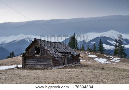Spring landscape with an old wooden barn. Cloudy day in a mountain village. View of the peaks. Carpathians, Ukraine, Europe