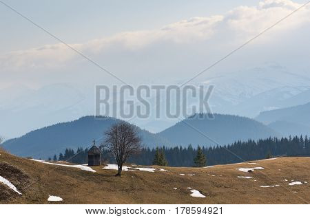 Spring landscape in the mountains. Old wooden chapel on a hill. Cloudy day