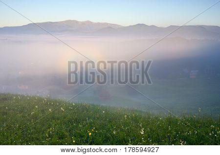 Summer landscape with fog and glory. Brockengespenst ghost in a mountain village. Morning landscape